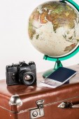 retro film camera with flight tickets and globe on vintage suitcase isolated on white
