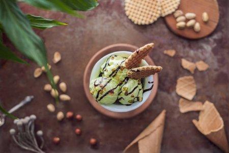 Photo pour Vue du dessus de la crème glacée aux pistaches avec gaufres en verre sur table - image libre de droit