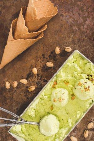 top view of pistachio ice cream with scoop and ice cream cones on table