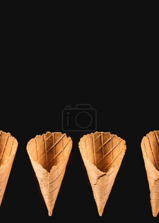 elevated view of row of ice cream cones isolated on black