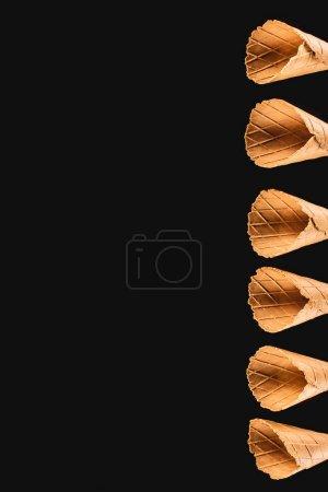 top view of row of ice cream cones isolated on black