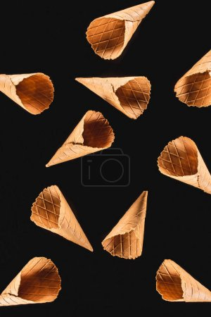 top view of scattered ice cream cones isolated on black
