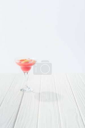 close up view of tasty summer alcohol cocktail on white wooden tabletop on grey background