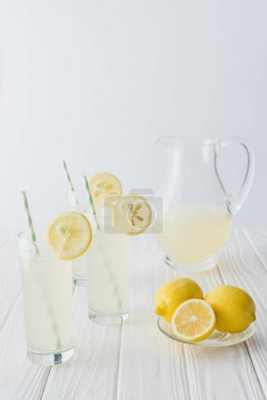 close up view of lemonade in jug and glasses with straws on white wooden tabletop on grey background