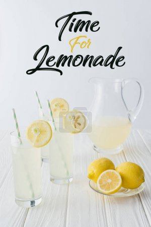 Photo for Close up view of time for lemonade lettering, lemonade in glasses and jug on wooden tabletop on grey backdrop - Royalty Free Image