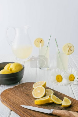 bouchent la vue de marguerites et de la limonade dans les verres sur une surface en bois blanche sur fond gris