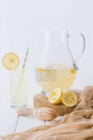close up view of jug and glass of lemonade on white wooden surface on grey backdrop