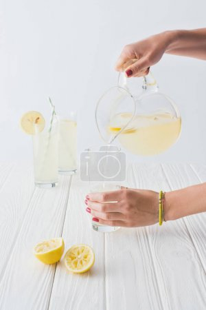 cropped shot of woman pouring lemonade into glass on grey background