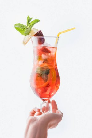 cropped shot of woman holding summer fresh strawberry cocktail with straw isolated on white