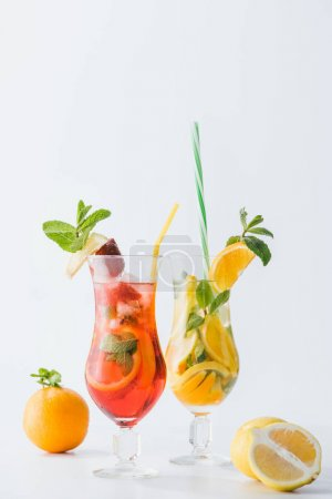 close up view of summer fresh cocktails with strawberry, lemon and oranges, mint and straws isolated on white