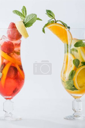 Photo for Close up view of summer fresh cocktails with lemon and orange pieces, mint isolated on white - Royalty Free Image