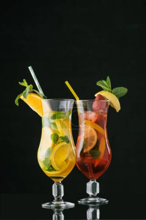 Photo for Close up view of summer fresh cocktails with mint and citrus pieces isolated on black - Royalty Free Image