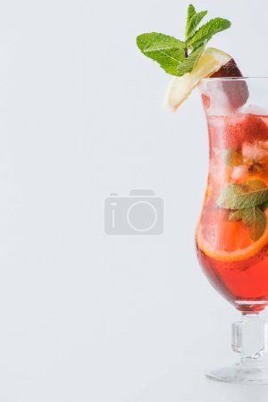 close up view of summer strawberry cocktail with ice, mint, lemon and orange pieces isolated on white