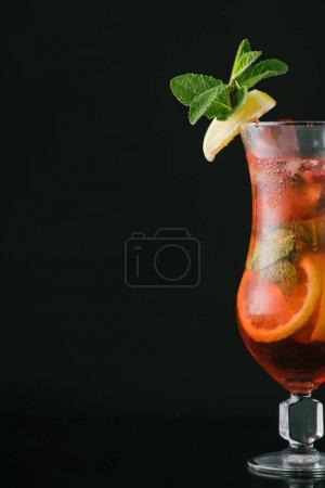 Nahaufnahme von sommerfrischem Cocktail mit Minz-, Zitronen- und Orangenstücken isoliert auf schwarz