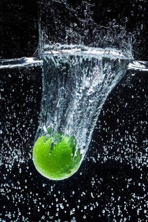 close up view of fresh lime in water with splashes isolated on black