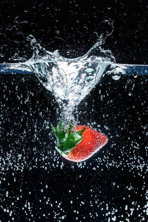 close up view of fresh strawberry in water isolated on black