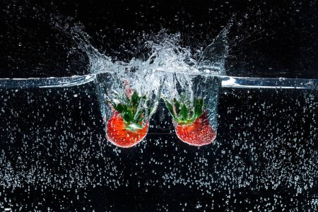 close up view of motion of ripe strawberries falling into water isolated on black
