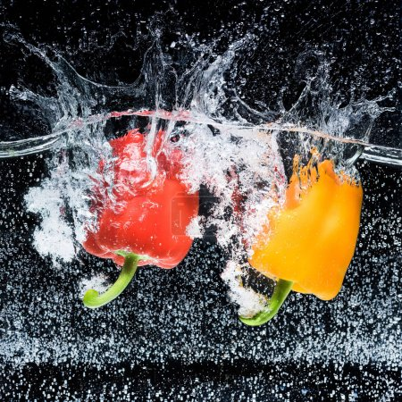 close up view of red and yellow bell peppers in water isolated on black