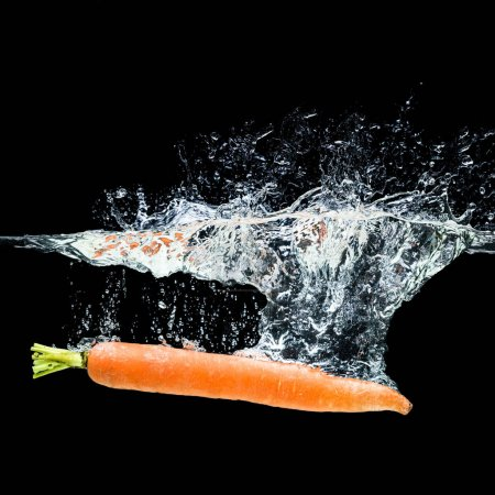 close up view of carrot in water isolated on black