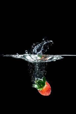 close up view of strawberry falling into water isolated on black