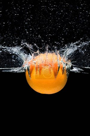 close up view of fresh orange citrus fruit falling into water isolated on black