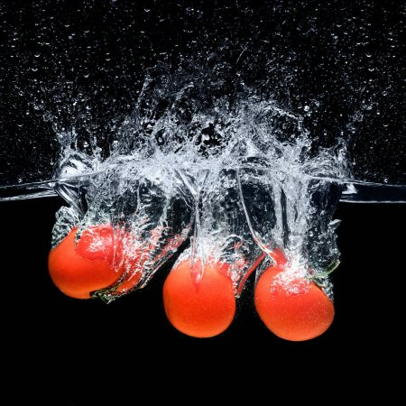 close up view of ripe tomatoes falling into water isolated on black