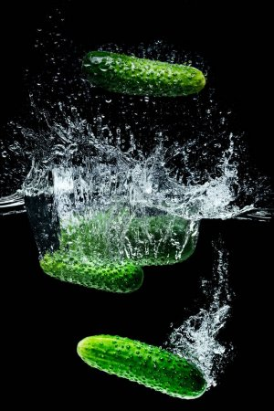close up view of ripe cucumbers falling into water with splashes isolated on black