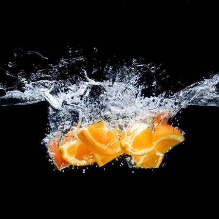 close up view of pieces of orange citrus fruit in water isolated on black
