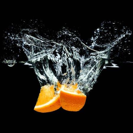Foto de Cerrar vista de piezas de frutas cítricas naranja en agua aislado en negro - Imagen libre de derechos