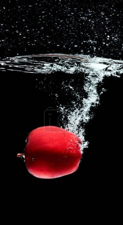 close up view of red apple falling into water isolated on black