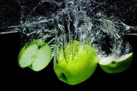 Photo pour Vue rapprochée des pommes vertes fraîches dans l'eau isolée sur noir - image libre de droit