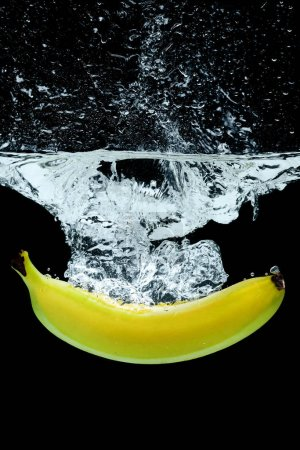 close up view of banana in water with splashes isolated on black
