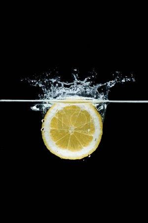 bouchent la vue sur le morceau de citron dans l'eau isolé sur fond noir