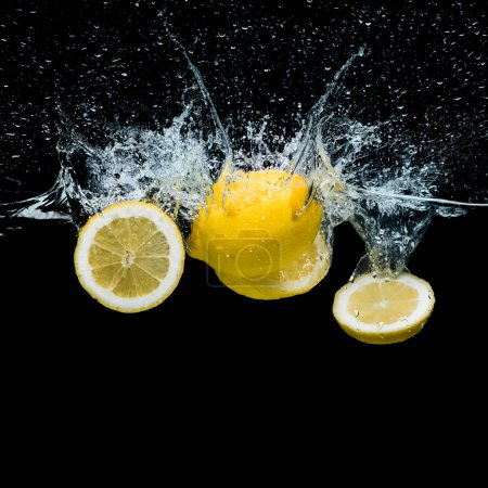 close up view of fresh lemon pieces in water with splashes isolated on black