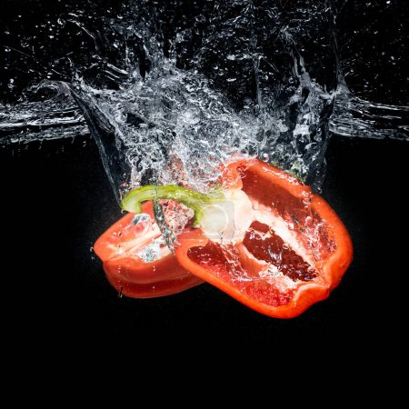 Photo for Close up view of bell pepper pieces in water isolated on black - Royalty Free Image