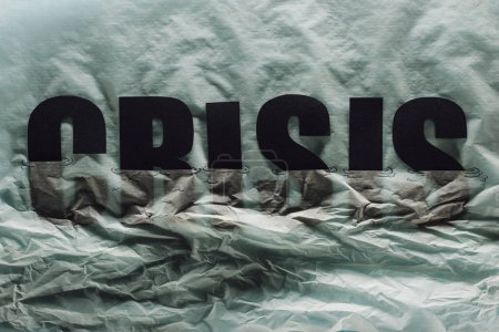 Photo for Black word crisis sinking in paper symbolizing water on grey paper background - Royalty Free Image