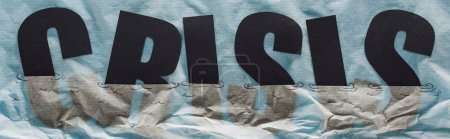 Photo for Panoramic shot of black word crisis sinking in paper symbolizing water on grey paper background - Royalty Free Image
