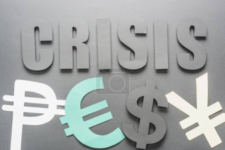 Photo for Top view of word crisis near peso, euro, dollar and yen symbols on grey background with shadow - Royalty Free Image