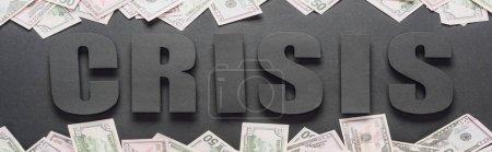 Photo pour Vue du dessus de la crise des mots près des billets de banque dispersés en dollars sur fond noir avec des ombres, prise de vue panoramique - image libre de droit
