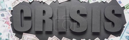 panoramic shot of word crisis in frame of dollar and euro banknotes on black background with shadows