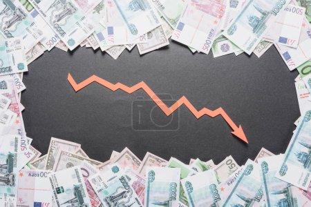 Photo pour Papier coupé flèche de la récession dans le cadre des billets en dollars, en euros et en roubles sur fond noir - image libre de droit