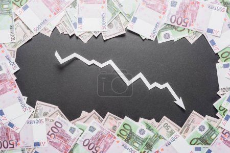 Photo for White paper cut recession arrow in frame of dollar and euro  banknotes on black background - Royalty Free Image