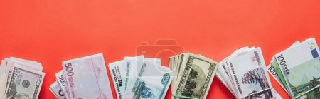 Photo for Panoramic shot of packs of dollar, euro and ruble banknotes on red background - Royalty Free Image