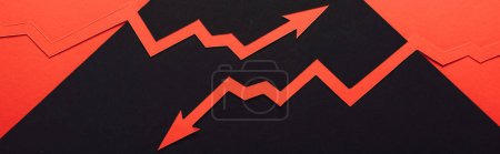 panoramic shot of paper cur recession and increase arrows on black and red background