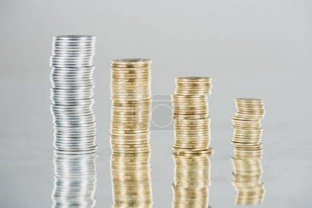 Foto de Montones de monedas de plata y oro sobre la superficie, con una reflexión aislada sobre el gris. - Imagen libre de derechos