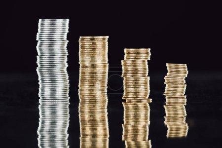 Photo pour Piles de pièces d'argent et d'or à la surface avec réflexion isolée sur noir - image libre de droit