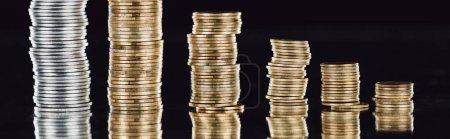 Photo pour Plan panoramique de pièces d'argent et d'or empilées à la surface avec réflexion isolée sur noir - image libre de droit