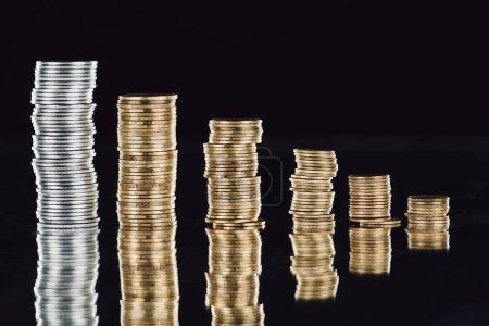 Foto de Montones de monedas de plata y oro sobre la superficie con una reflexión aislada sobre negro. - Imagen libre de derechos