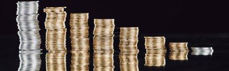 Foto de Foto panorámica de monedas de plata y oro apiladas sobre la superficie con reflexión aislada sobre negro. - Imagen libre de derechos