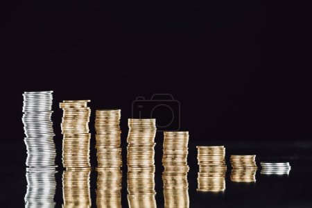 stacks of silver and golden coins on surface with reflection isolated on black